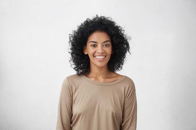 幸せな笑顔でスタジオでポーズをとって巻き毛の陽気な若い混血女性の肖像画を上半身