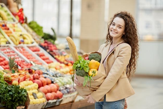 ファーマーズマーケットでポーズをとって笑っている間、新鮮な食料品が入った紙袋を持っている陽気な若い女性の肖像画を腰に当てる