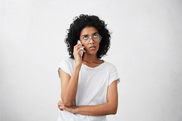 Портрет обеспокоенной африканской бизнес-леди, решающей свои проблемы по мобильному телефону