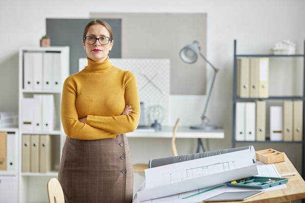 사무실에서 책상을 그리는 팔을 넘어 서있는 동안 자신감 여성 건축가의 초상화를 허리 위로,