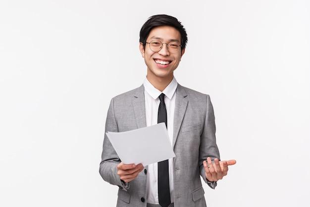 自信を持ってハンサムなプロの男性オフィスマネージャー、灰色のスーツを着たビジネス起業家、彼のプロジェクトの紹介、紙からのスピーチの読み取り、ドキュメントの保持、笑顔のウエストアップポートレート