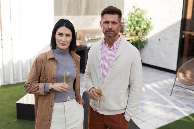 Поднимите талию портрет современной взрослой пары, стоя на открытой террасе с флейтами для шампанского