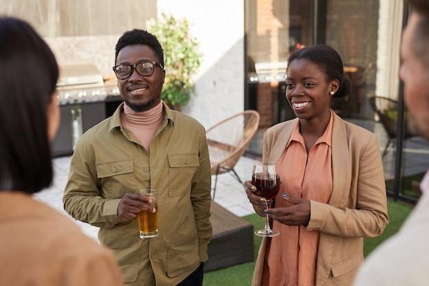 パーティー中に屋外テラスに立っている間、友人とチャットしている現代のアフリカ系アメリカ人のカップルの肖像画を腰に当てる