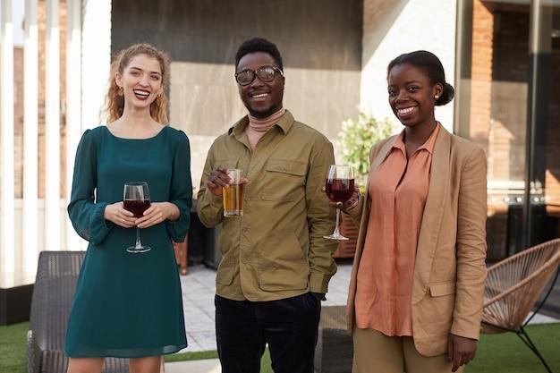 Портрет современного афроамериканца с поднятым вверх талией, наслаждаясь вином на открытой террасе во время вечеринки