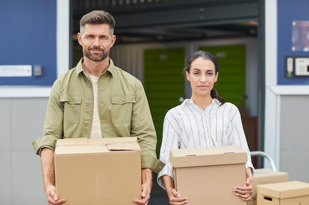 箱を持っている現代のカップルの肖像画を腰に上げ、セルフストレージ施設のそばに立っている間、スペースをコピーします
