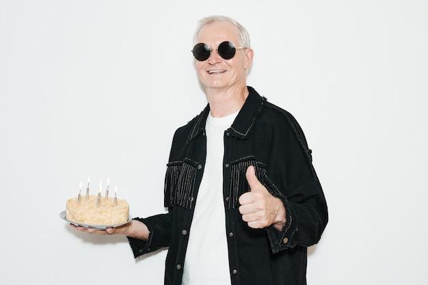 フラッシュで撮影、パーティーで白い背景にバースデーケーキを保持しているクールな年配の男性の肖像画をウエストアップ