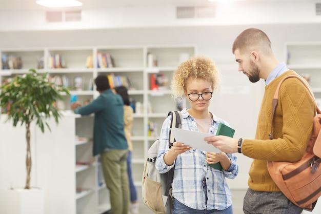 Портрет пары студентов, читающих документы, стоя в библиотеке колледжа
