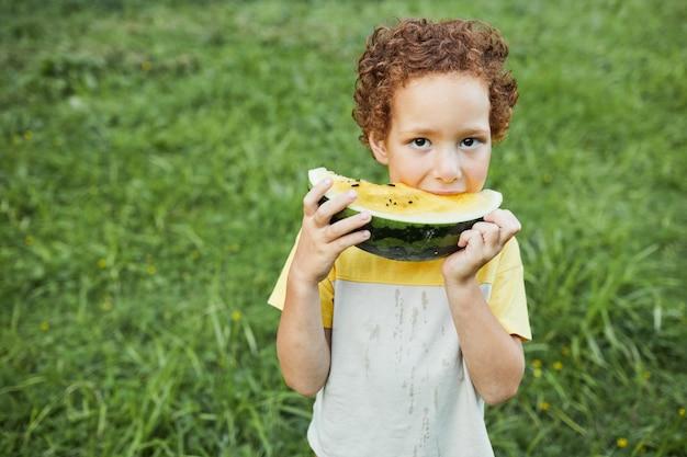 屋外でスイカを食べてカメラを見ている巻き毛の少年の肖像画をウエストアップ