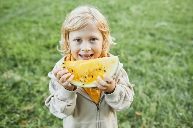屋外でスイカを食べて、カメラのコピースペースで笑っているかわいい男の子の肖像画をウエストアップ