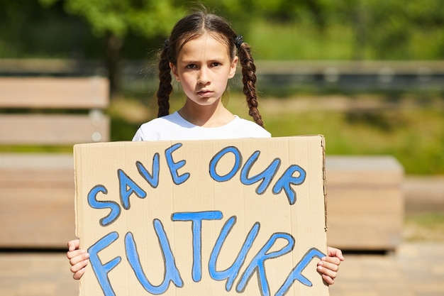 屋外で自然と経済に抗議しながら、savefutureの書き込みでサインを保持しているかわいい女の子の肖像画を腰に当てる