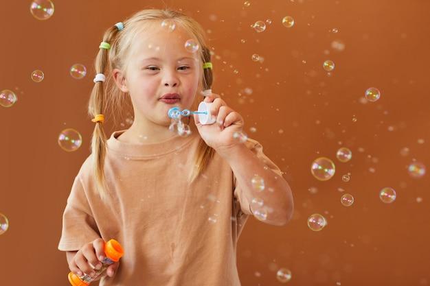 스튜디오에서 갈색 표면에 포즈를 취하는 동안 거품을 불고 다운 증후군이있는 귀여운 소녀의 초상화를 허리, 복사 공간