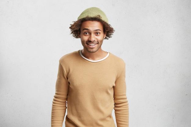 暗い肌の面白い男性の上半身の肖像画は、帽子とセーター、ポーズを着ています。