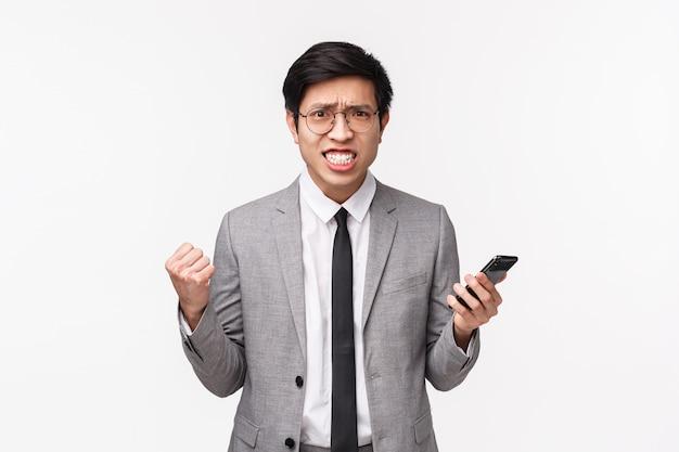 Талия-вверх портрет недовольного, обеспокоенного и раздраженного азиатского бизнесмена в сером костюме, сжимающего зубы и кулаки, хмурого взгляда агрессивного, морщащегося, раздраженного от чтения плохих новостей на мобильном телефоне