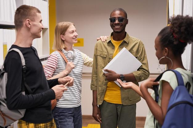 笑顔の盲目の男とチャットしている学生の多様なグループの肖像画を腰に当てる