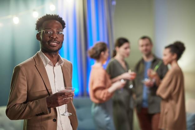 실내에서 파티를 즐기는 동안 카메라를 보고 칵테일 잔을 들고 있는 우아한 아프리카계 미국인 남성의 허리 초상화, 복사 공간