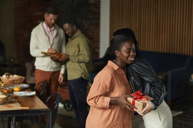 집에서 저녁 파티를 위해 손님을 환영하면서 친구를 포옹하는 우아한 아프리카 계 미국인 여자의 초상화를 허리,