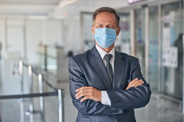 출발 전 공항 홀에 서 있는 보호 마스크와 정장을 입은 우아한 남성의 허리 초상화