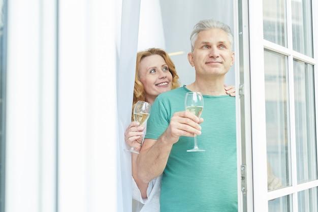 집이나 호텔에서 창 밖을 보면서 샴페인을 즐기는 우아한 성숙한 부부의 초상화를 허리, 복사 공간