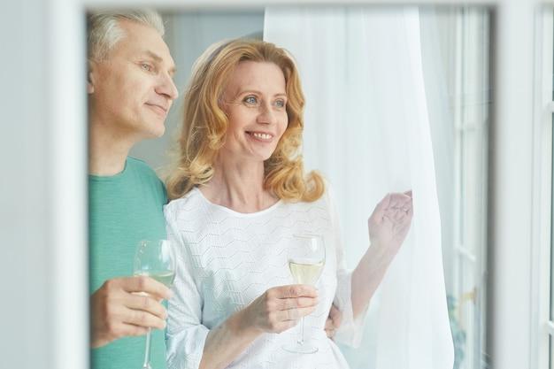 창 밖을 보면서 샴페인을 즐기는 우아한 성숙한 부부의 초상화를 허리, 유리 뒤에서 촬영, 공간 복사