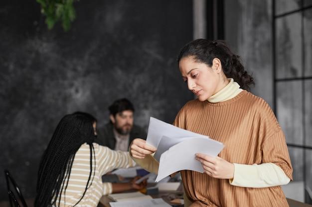 Подняв талию портрет элегантной ближневосточной бизнес-леди, читающей документы в офисе с разнообразной группой людей, встречающихся в фоновом режиме, копировальное пространство
