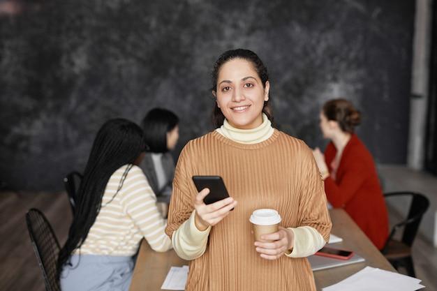 Талия вверх портрет элегантной ближневосточной бизнес-леди, улыбающейся в камеру в офисе с разнообразной группой людей, встречающихся в фоновом режиме, копией пространства