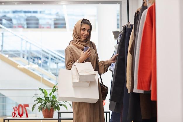 의류 선반 옆에 서서 쇼핑몰에서 쇼핑을 즐기는 동안 우아한 중동 여자의 초상화를 허리 위로 복사 공간 복사