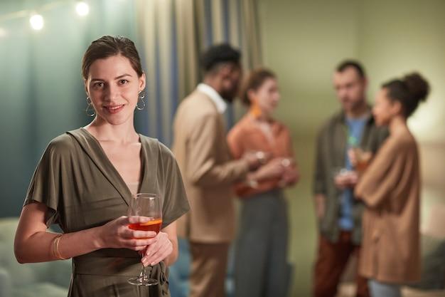 실내에서 파티를 즐기는 동안 카메라를 보고 칵테일 잔을 들고 있는 우아한 젊은 여성의 허리 초상화, 복사 공간