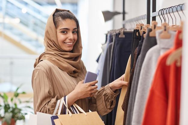 의류 선반 옆에 서서 쇼핑몰에서 쇼핑을 즐기는 동안 우아한 젊은 여성의 초상화를 허리 위로 올리십시오.
