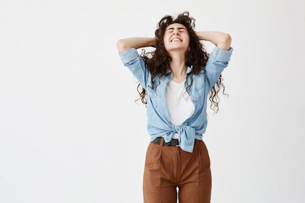 Талистный портрет эмоциональной темноволосой модели женщины носит джинсовую рубашку, сжимает ее ровные белые зубы в радости, с закрытыми глазами, держит руки на голове. выражение лица, эмоции и чувства