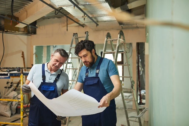 Портрет отца и сына, глядя на планы этажей во время совместного ремонта дома, с копией пространства