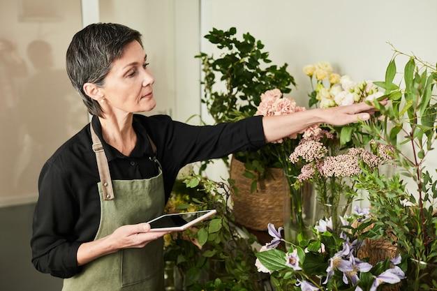 Портрет женщины-флориста, занимающейся инвентаризацией запасов, работая в небольшом бизнесе цветочного магазина ...