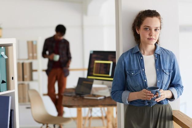 백그라운드에서 컴퓨터 코드로 머그잔을 코딩하는 동안 카메라를보고 여성 it 프로그래머의 초상화를 허리, 복사 공간