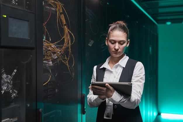 Портрет женского сетевого инженера, использующего цифровой планшет во время настройки серверов в центре обработки данных, с копией пространства