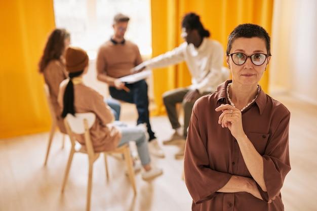 지원 그룹에서 치료 세션 동안 카메라를 보고 있는 여성 심리학자의 허리 초상화, 복사 공간