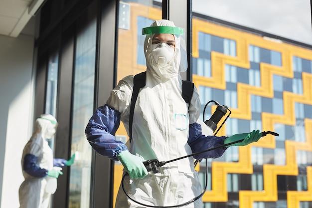 방호복을 입고 사무실에 서있는 동안 소독 장비를 들고 여성 노동자의 초상화를 허리 위로 올리십시오.