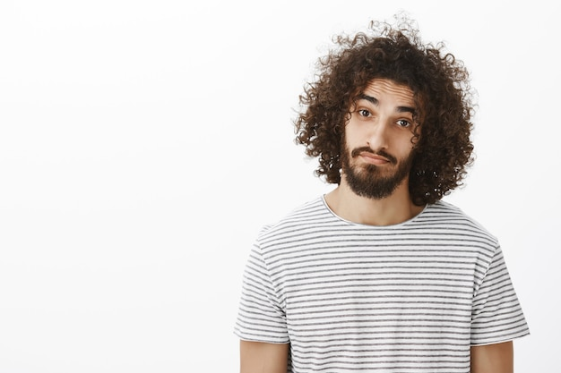 Портрет дружелюбного симпатичного латиноамериканского парня с бородой и афро-прической, одетый в повседневную полосатую футболку, с поясом