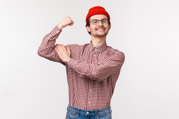 赤いビーニーとクールでタフな眼鏡をかけた面白い大人のスリムな男性の上半身の肖像
