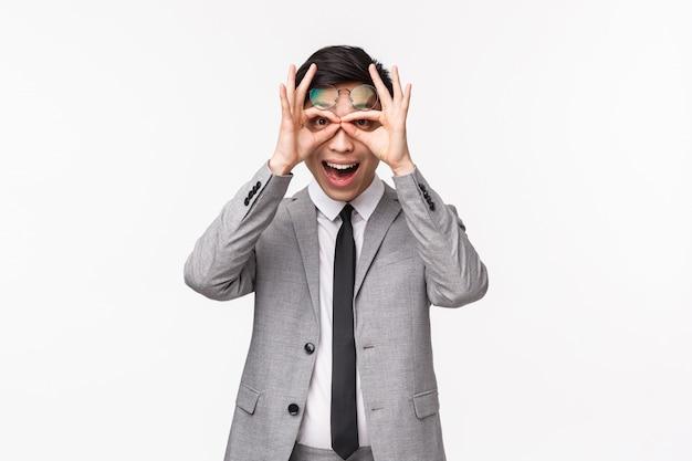 Талия-вверх портрет забавного и удивленного, возбужденного азиатского мужчины-предпринимателя в деловом костюме, делающего очки пальцами и смотрящего на него с впечатленным лицом, видя потрясающую рекламу