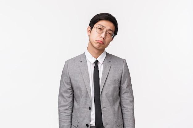 スーツを着た憂鬱でしぶしぶ、感銘を受けていない退屈なアジア人男性の腰までの肖像