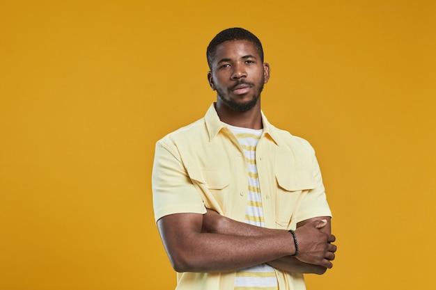 自信を持ってポーズをとっている間、カメラを見ているハンサムなアフリカ系アメリカ人男性の肖像画を腰に当ててください...
