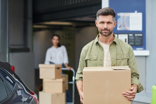 상자를 들고 잘 생긴 남자의 초상화를 허리 위로 올리고 셀프 보관 시설에 서있는 동안 공간을 복사하십시오.