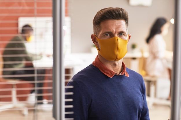 마스크를 쓰고 사무실 인테리어에 서있는 동안 카메라를보고 잘 생긴 성숙한 남자의 초상화를 허리, 복사 공간
