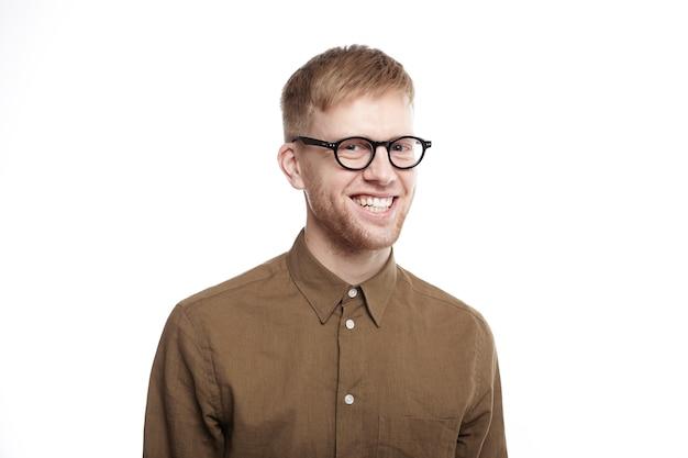 トレンディなメガネをかけた無精ひげと広くニヤリと笑うフォーマルなシャツを着た幸せな恍惚とした若い男の肖像画を腰に当て、仕事で昇進し、優れた仕事のボーナスを得た後、大喜びを感じます