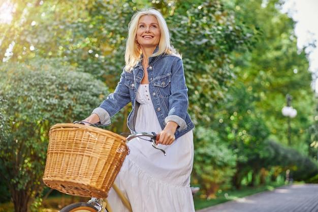 여름 녹색 도시 대로를 통해 빈티지 자전거를 타고 행복한 웃고 있는 여성의 허리 위 초상화
