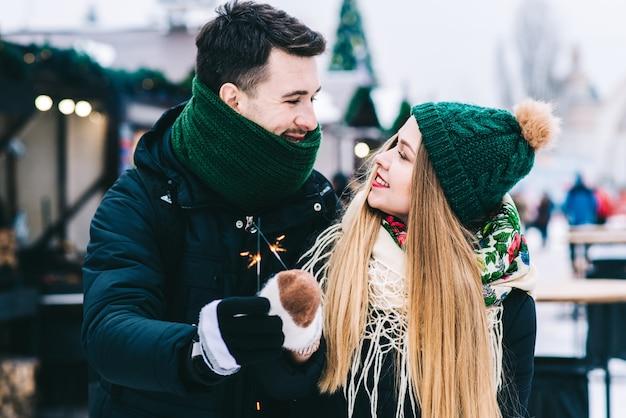 공원에서 겨울 날씨에 감탄하는 행복한 사랑의 커플의 허리 위로 초상화. 그들은 서로를 바라보면서 껴안고 웃고 있습니다. 반짝임을 들고 사람들
