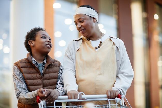 Портрет счастливой матери и сына, делающий покупки в супермаркете и толкающих тележку для продуктов