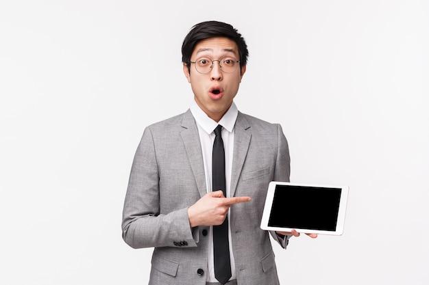 Талия-вверх портрет впечатленного, любопытного азиатского молодого человека в сером костюме и очках, задавая вопрос о чем-то, что он видел в интернете, указывая на экран цифрового планшета, выглядят заинтригованными