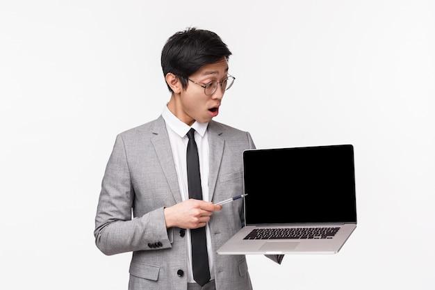 Портрет талисмана впечатленного, возбужденного азиатского мужчины-предпринимателя, пораженного хорошей диаграммой, большим доходом, с упавшей челюстью на дисплее ноутбука, читающей шокирующую информацию на белой стене
