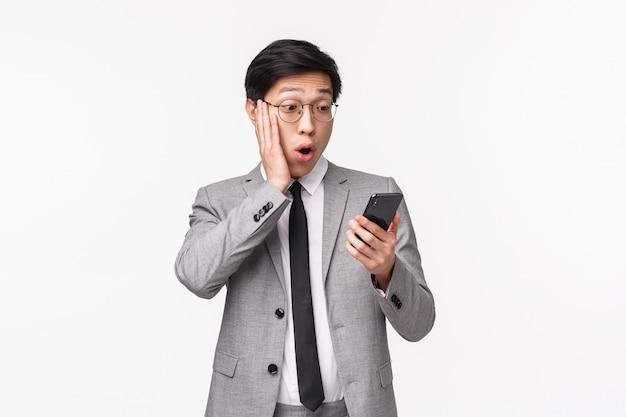 Талия-вверх портрет впечатленного, безмолвного азиатского красивого бизнесмена в сером костюме, задыхающегося от прикосновения щеки, пораженного, как он смотрит на дисплей смартфона, читая шокирующие новости или сообщение