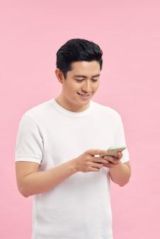 スマートフォンでインターネットを閲覧しながら灰色の壁に寄りかかって楽しいベトナム人男性のウエストアップポートレート、スタジオ撮影